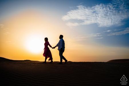 Pareja caminando en la puesta del sol del desierto por Dubai fotógrafo de bodas