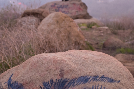 Hollywood, Kalifornien, Verlobungsporträts in den Hügeln Der Fotograf entdeckt eine Zeichnung auf dem Felsen, während das Paar auf der anderen Seite Spaß hat.