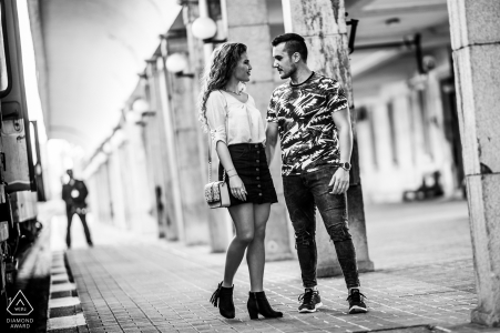 Black and white engagement portrait of the couple giving each other a last kiss goodbye at the train station in Ruse, Bulgaria.