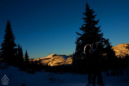 Ein Paar wird als die Sonne silhouettiert, die auf Schrein-Durchlauf in Vail Colorado während ihrer Fallverpflichtungssitzung einstellt
