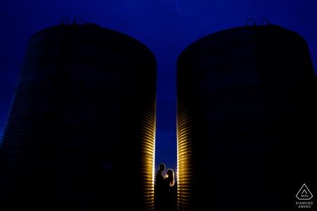 Sesión fotográfica de Dodd Lake Rural Engagement entre un par de silos en una granja en Boulder, Colorado