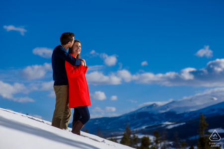 Sapphire Point Engagement Photography Session - Kisses in the snow wearing a red winter coat as Breckenridge resort is seen in the background