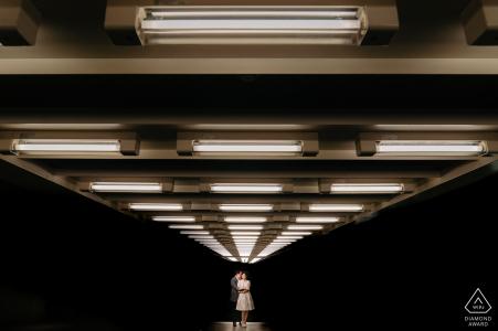 Betrokkenheidsfoto van een paar in de verte verlicht van boven in Antwerpen.