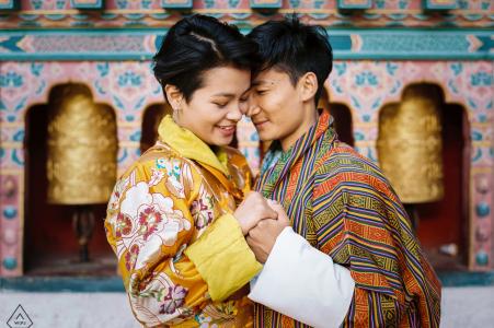 Photo de fiançailles d'un couple debout devant un temple à Thimphu, au Bhoutan.