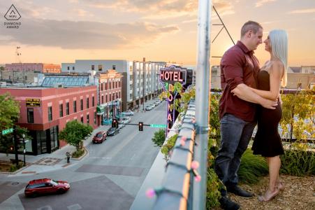 Un couple nouvellement fiancé apprécie des moments ensemble sur le toit de HoDo au coucher du soleil à Fargo, Dakota du Nord, pendant la séance photo de fiançailles