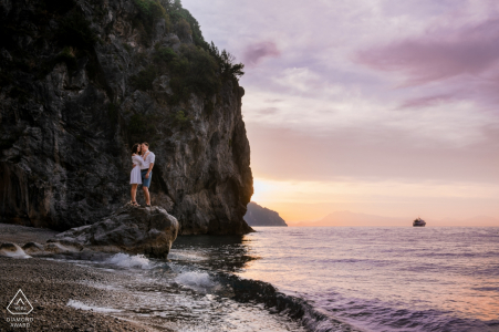 Amalfi, Italy - A couple stands on a boulder as the sun sets over the ocean in this engagement portrait shoot
