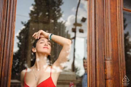 Prague future bride stands in the window as her fiance watches behind her in this engagement photo shoot