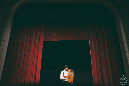This image of a couple kissing in an opening in a red stage curtain was captured during this Lazio engagement photo session