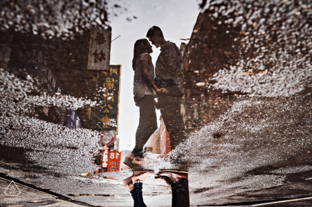 A couples reflection is captured in a puddle on the street in this New York City engagement portrait shoot