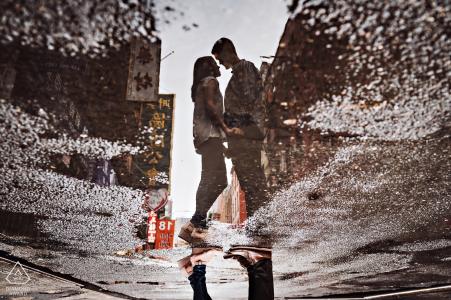 Eine Paarreflexion wird in einer Pfütze auf der Straße in diesem New York City-Verlobungsporträtschießen gefangen genommen