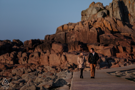 Sessione di ritratto di fidanzamento al faro di Corbiere, Saint-Brélade, Jersey, CI - Tiro di fidanzamento costiero di una coppia che cammina insieme