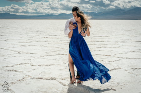Le tournage des fiançailles de Death Valley se déroule au milieu d'un désert tandis que les montagnes se tiennent au loin derrière le couple qui les embrasse