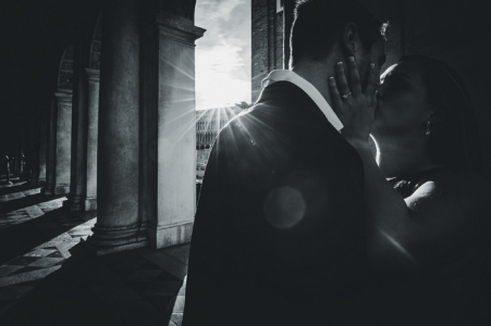 Un couple embrasse pendant que le soleil traverse de grandes colonnes dans ce portrait en noir et blanc de mariage réalisé par un photographe de Venise, en Vénétie.