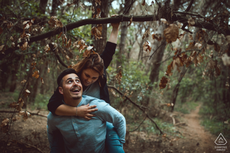 A man carries his fiance on his back as she holds onto a tree branch in the woods of San Felice Circeo in this engagement session by a Latina, Lazio photographer.