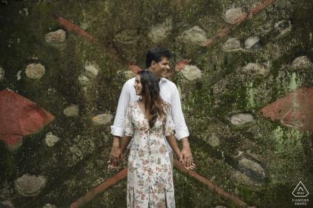 Un couple pose ensemble devant un dessin unique dans le Parque Lage lors de cette séance photo de fiançailles réalisée par un photographe de Rio de Janeiro, au Brésil.