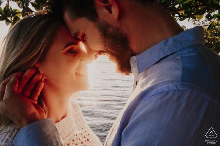 Un hombre y una mujer mantienen sus cabezas juntas mientras el sol brilla entre ellos durante su sesión de compromiso en Laguna por un fotógrafo de Santa Catarina, Brasil.