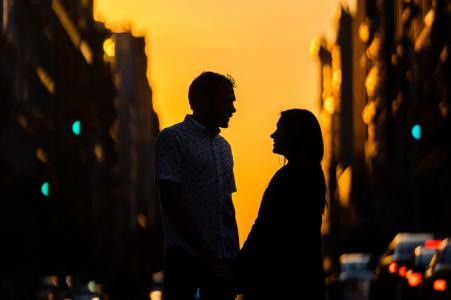 Un couple silhouette partage un moment lors de leur séance de photos d'engagement à New York