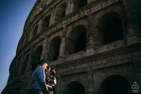 Un couple debout et touchant le nez devant le Colisée romain lors de cette séance de photos de fiançailles par un photographe de Lazio, en Italie.