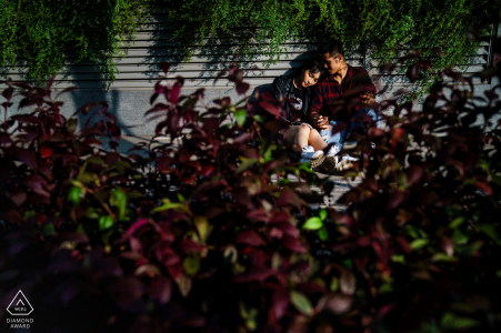 A couple sits together in Saigon partially hidden behind a bush in this pre-wedding photo by a Ho Chi Minh, Vietnam photographer.