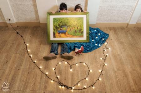 Un couple assis par terre tenant un tableau tandis qu'une rangée de lumières en forme de cœur s'étale devant eux pour leur séance photo précédant le mariage par un photographe du comté de Hualien, à Taiwan.