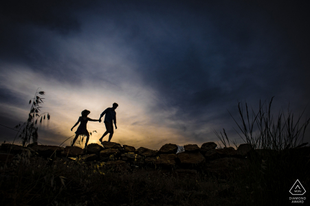 Silhouetted couple hold hands as they walk in Mersin, Turkey during their engagement shoot