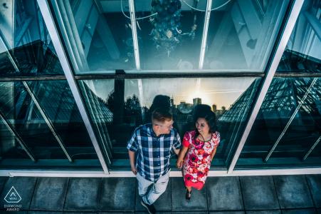 Un couple se tenant contre un bâtiment à Edmonton devant de grandes fenêtres sur cette photo de fiançailles prise par un photographe d'Alberta, Canada
