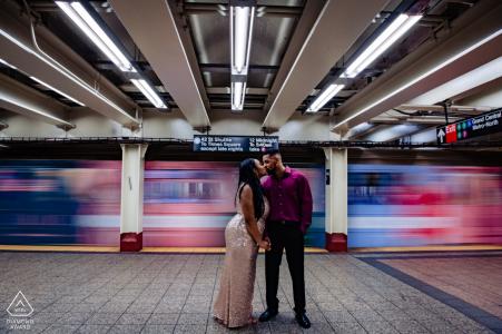 Un tren subterráneo pasa mientras la pareja comprometida se besa durante su sesión de compromiso en la estación Grand Central.