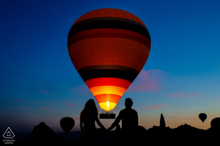 Engaged couple hold hands at night in cappadocia, turkey for their engagement photo session