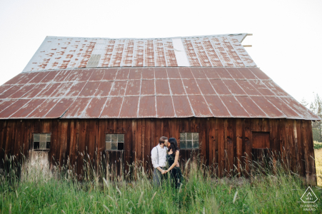 Enumclaw, WA Portrait Session vor der Hochzeit | Ein frisch verlobtes Paar küsst sich neben einer Scheune