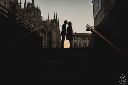 Una fotografía de compromiso de Nápoles de una pareja besándose en una escalera de la ciudad de Milán al atardecer