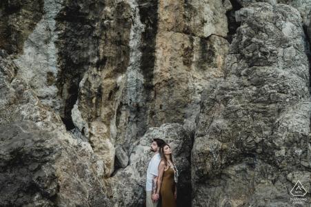 Una pareja se encuentra de espaldas frente a un acantilado de piedra en este retrato de compromiso fotografiado por un fotógrafo de Nápoles cerca de Positano
