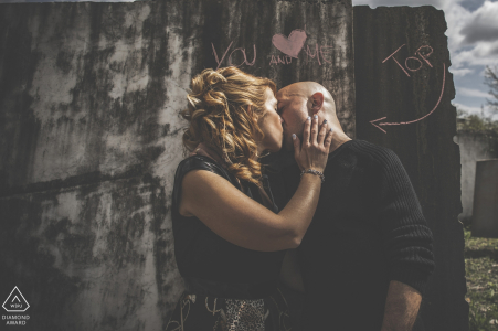 This photo of a couple kissing in front of a wall with graffiti was captured by a Ceparana engagement photographer