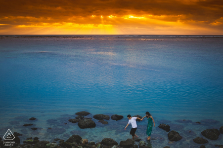 Bali pareja caminando en la puesta de sol en la playa rocas para retrato de compromiso
