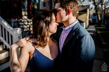 Man kisses a woman's forehead during a Roscoe Village engagement shoot in Chicago.