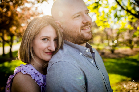 A couple hugs each other during an engagement shoot in Wilder Park in Elmhurst, IL.