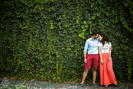 Patones, Spain - A couple posing in front of a vertical garden for engagement portrait