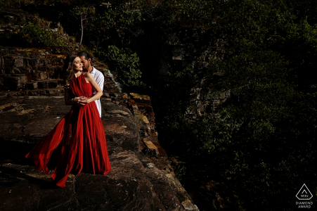 Couple de Pirenópolis avec une robe rouge lors d'une séance de portrait avant le mariage