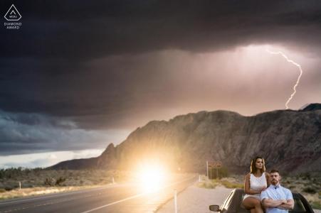 Séance photo d'engagement - Red Rock Nevada - Un couple pose au sommet de la voiture et à l'arrière-plan, le moment exact de la foudre