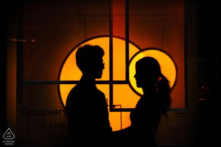 Soho pareja comprometida de pie delante de una ventana con iluminación en el fondo para retratos
