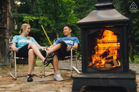 Photographe de mariage dans les Cantons-de-l'Est, au Québec - Un couple de fiancés se détend dans leur jardin au coin d'un feu pendant une séance photo.
