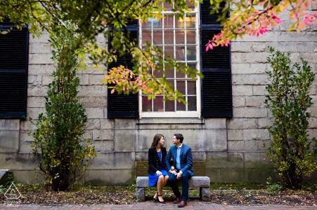 Photographie de fiançailles à Portland dans le Maine - Le couple est assis côte à côte sur un banc à Portland dans le Maine
