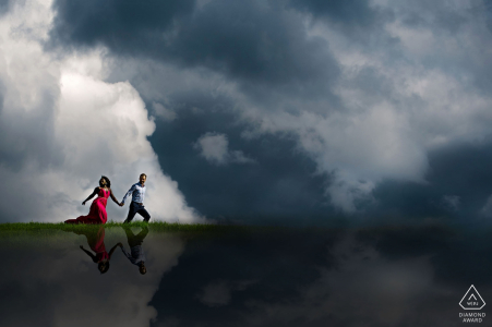 Couple running in the clouds over Edmonton, Alberta during engagement portrait session.
