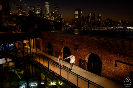 Brooklyn Dumbo Engagement Photos - Pareja paseando en Dumbo con vista nocturna de Manhattan