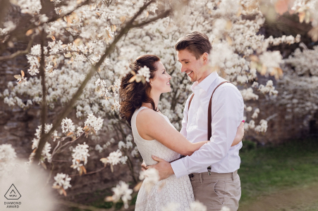 Engagement Photos from Rittergut Stoermede - Image contains: couple, trees, flowers, portrait, hug, smiles