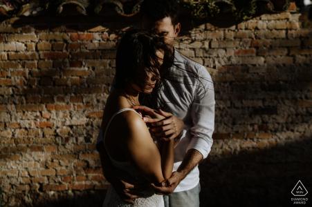 Engagement Photos from O Butia - Porto Alegre - Rio Grande do Sul - Portrait contains: brick, wall, shadows, couple, love session