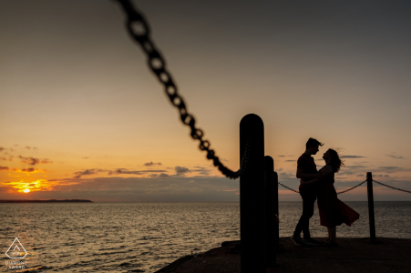 Ritratto di fidanzamento da Whitstable Harbour, Kent, Regno Unito | La coppia si abbraccia alla fine del molo al tramonto
