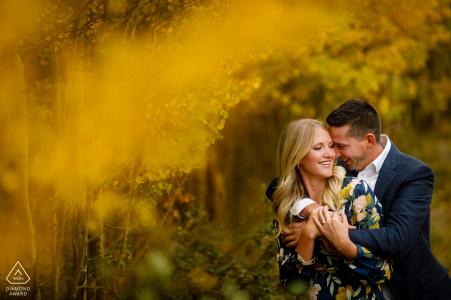 Breckenridge-paar die op elkaar houden in een bosje van gele espbomen.