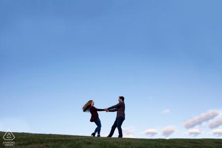 Millcreek Ravine, Edmonton Engagement Photography: un couple tourbillonne au sommet d'une colline