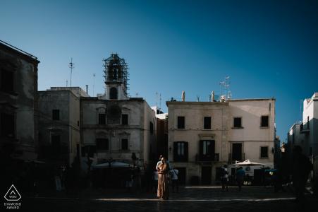 Sesión de compromiso previa a la boda en Puglia con edificios y cielos azules