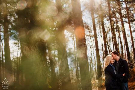 Heath, West Sussex Woodland love portrait d'un couple dans les arbres et la lumière du soleil.